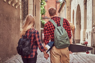 Handsome skater and his girlfriend walking around an old narrow streets of Europe.