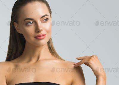 Woman skin care hair care long beauty brunette hair natural skin make up over blue
