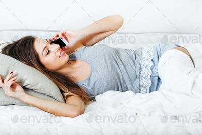 Young woman home with mobile phone at home calling. Indoor shot.