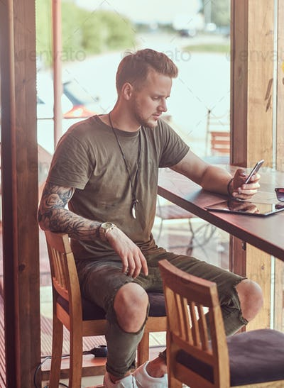 Handsome stylish hipster sits at a table in a roadside cafe, reading the message on the smartphone.