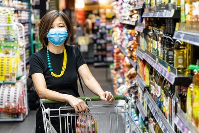Asian woman shopping groceries in supermarket with protective face mask as new normal requirement