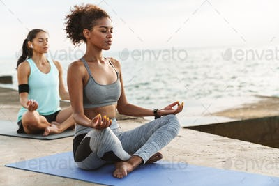 Two healthy fitness women doing yoga exercises on fitness mats