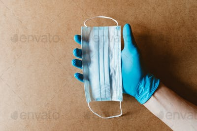 Hand in blue rubber gloves holds a medical mask. Health care and antivirus protection concept