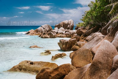 La Digue, Seychelles Islands. Turquoise ocean lagoon at popular Anse Cocos beach with granite rock