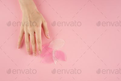 Woman touching pink leaves on pastel background top view copy space, concept