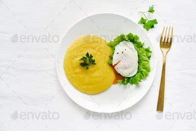 Poached egg and polenta with lettuce salad, fodmap diet, top view copy space closeup