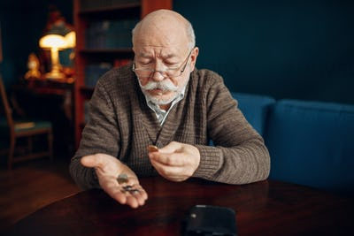 Pour elderly man holds coins