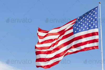 American flag waving in the wind on blue sky