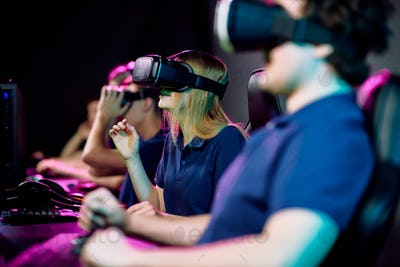 Teenage cybersports gamer in virtual reality goggle watching video game