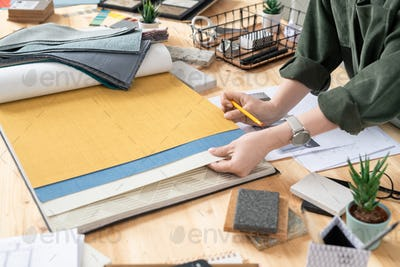 Hands of young female creative designer of interior choosing wallpapers