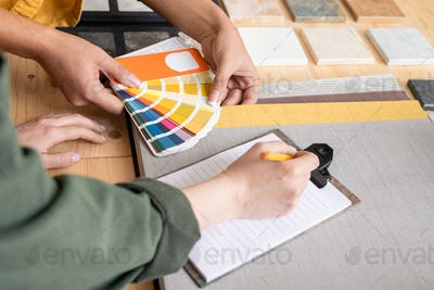 Hands of designer holding palette over table while showing colors to colleagu