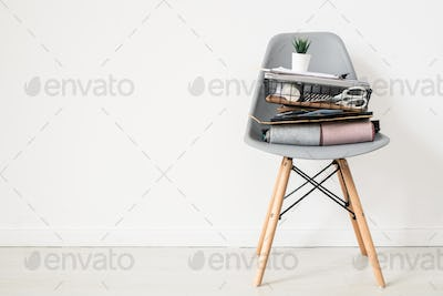 Grey plastic office chair with folded textile samples and basket with supplies