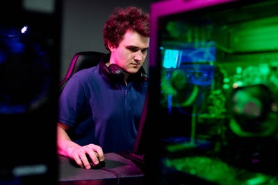 Serious guy with headphones looking at computer screen during e-sport cyber game
