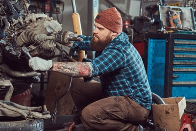 Brutal tattooed mechanic repairs the car engine which is raised on the hydraulic lift in the garage