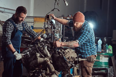 Two bearded mechanics repairs the car engine which is raised on the hydraulic lift in the garage.