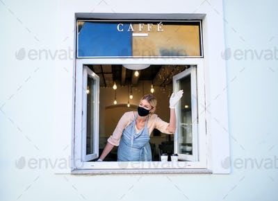 Woman with face mask serving coffee through window, shop open after lockdown