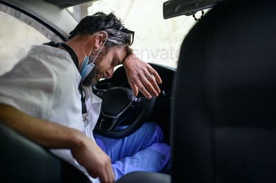 Tired and exhausted doctor sitting in car after long and difficult shift, sleeping