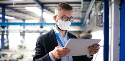 Technician or engineer with protective mask and tablet working in industrial factory