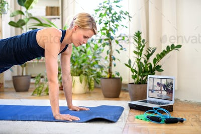 Woman indoors doing fitness workout at home, watching online video tutorial