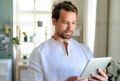 Front view portrait of man using tablet at home