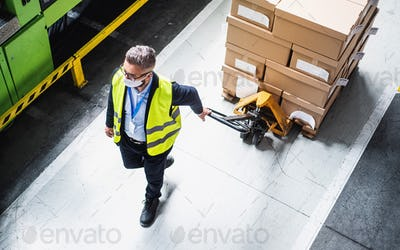 Top view of man worker with protective mask working in industrial factory or warehouse