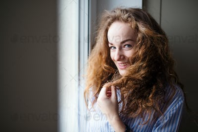 Close-up portrait of young woman standing by window indoors at home