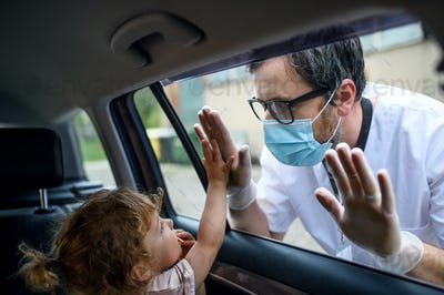 Doctor coming to see daughter in isolation, car window glass separating them