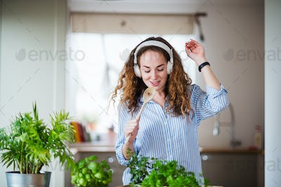 Young woman with headphones relaxing indoors at home