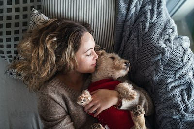 Top view of young woman relaxing indoors on sofa at home with pet dog