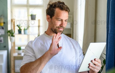 Portrait of mature man having video call on tablet at home