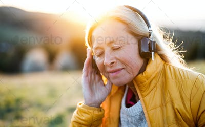 Senior woman sitting outdoors in nature at sunset, relaxing with headphones