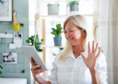 Senior businesswoman with tablet indoors in home office, business call concept