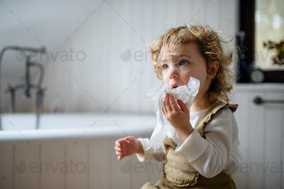Small sick girl with cold at home sitting on ground, blowing nose