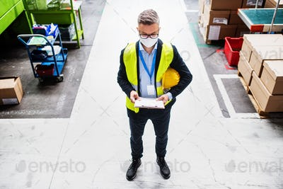 Top view of technician or engineer with protective mask standing in industrial factory