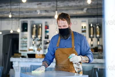 Coffee shop man owner working with face mask and gloves, disinfecting tables