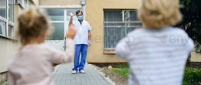 Children greeting father doctor from distance in front of hospital, coronavirus concept