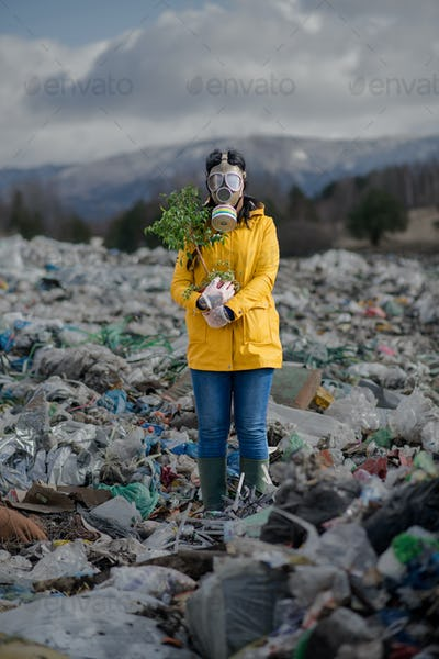 Woman with gas mask holding green plant on landfill, environmental concept