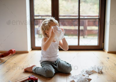 Small sick boy with cold at home sitting on ground, sneezing