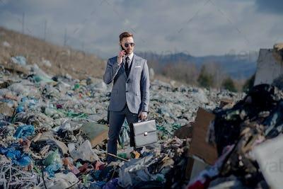 Businessman with smartphone on landfill, consumerism versus pollution concept