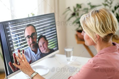 Young woman having video call with husband and son, social distancing concept