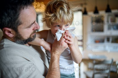 Father blowing nose of small sick son indoors at home