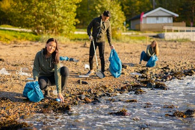 Young woman in a team picking up garbage in bag at beach