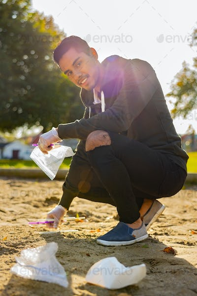 Back lit of smiling man cleaning garbage on sand at park