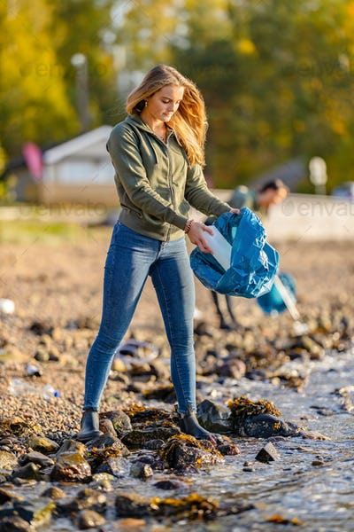 Young woman picking up garbage from rocky shore