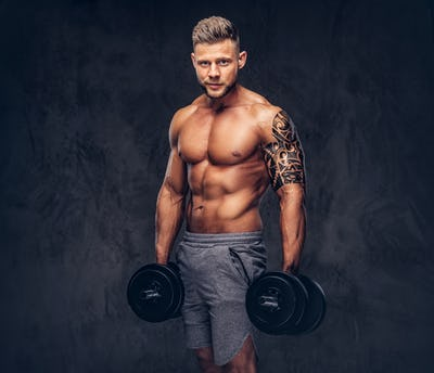 Handsome shirtless tattooed bodybuilder wearing sports shorts, posing in a studio.
