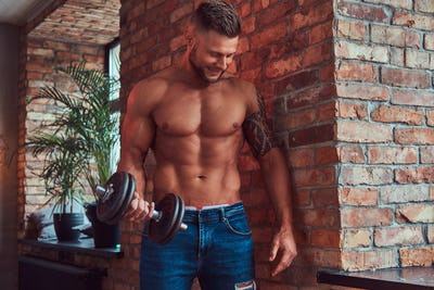 Portrait of a strong handsome shirtless male with muscular body in an apartment