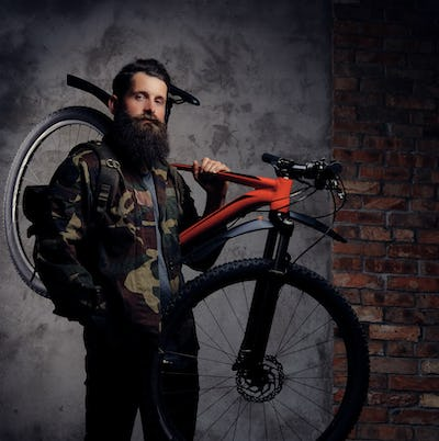 Handsome bearded traveler, dressed in a trendy camouflage jacket, standing with sports bicycle