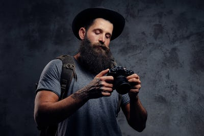 Handsome bearded traveler in a hat with a backpack and tattooed arms, holds a photo camera