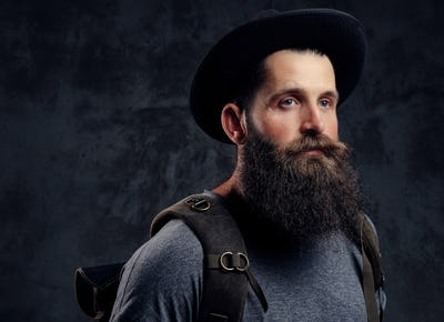 Portrait of a handsome bearded traveler in hat with backpack. Isolated on a dark background.