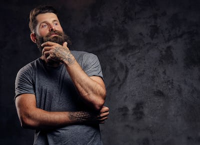 Portrait of a hipster with full beard and stylish haircut, dressed in a gray t-shirt in a studio